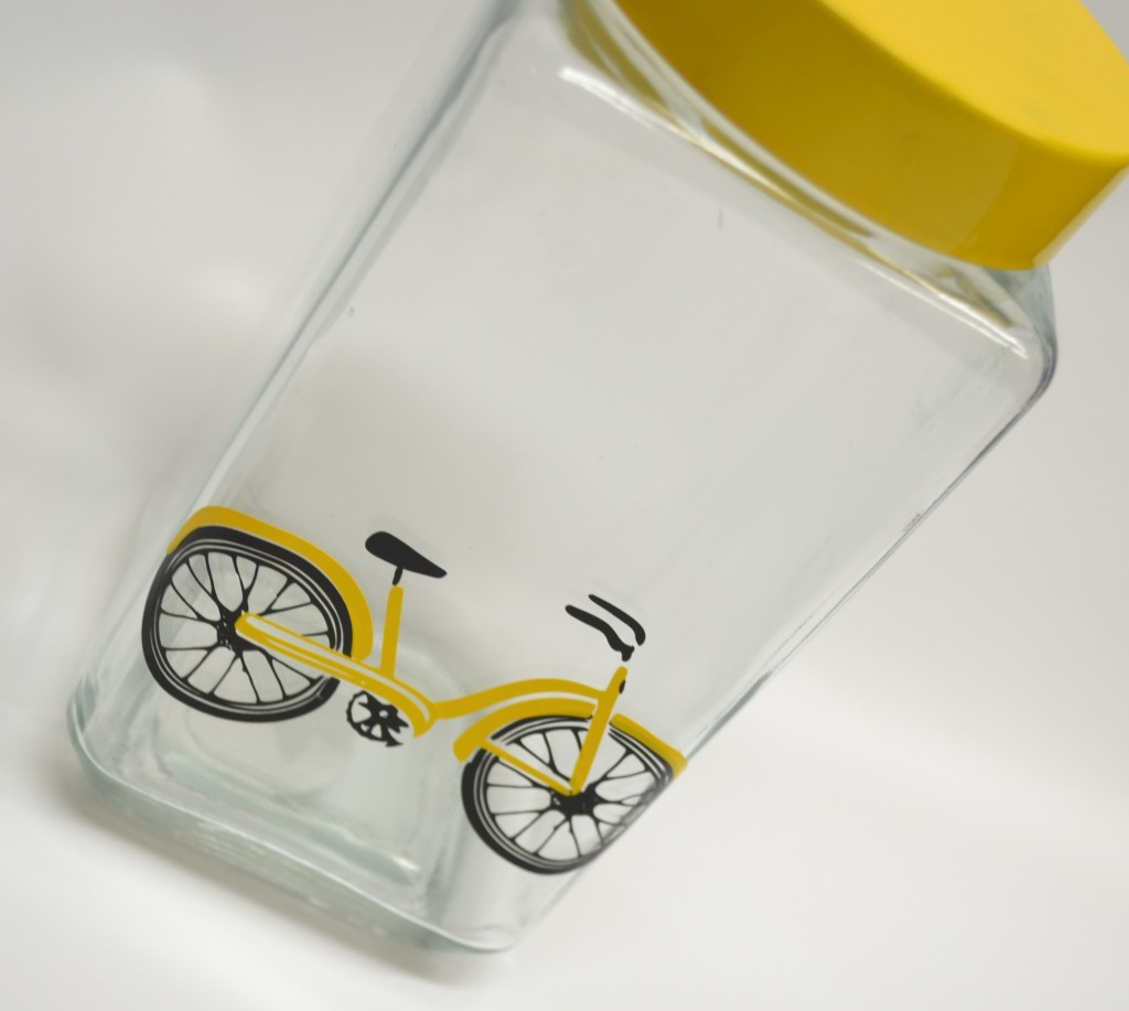 Picture of glass jar with yellow lid and yellow and black bike